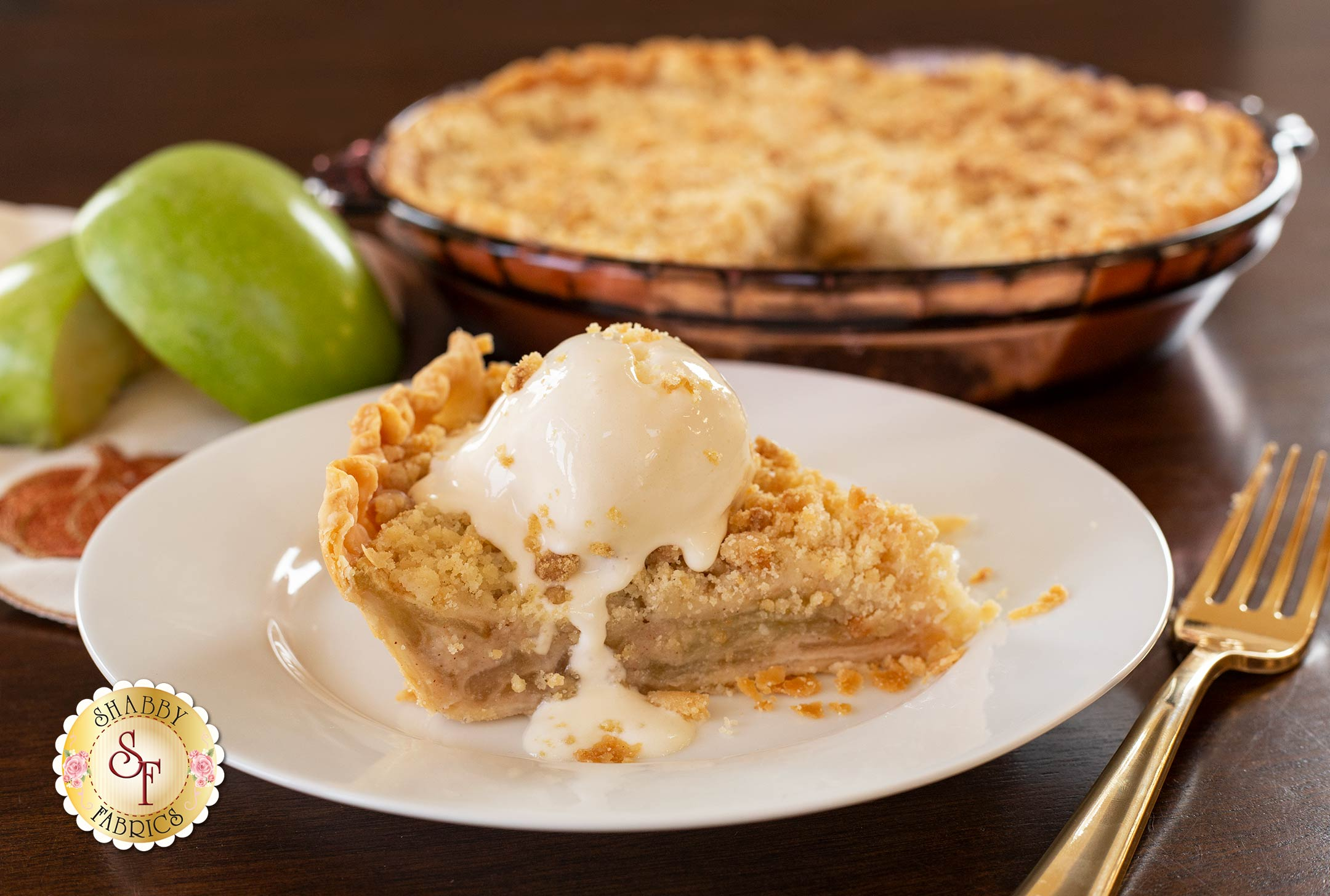 Lynn's Dutch Apple Pie cut into a slice and served with ice cream and apple slices