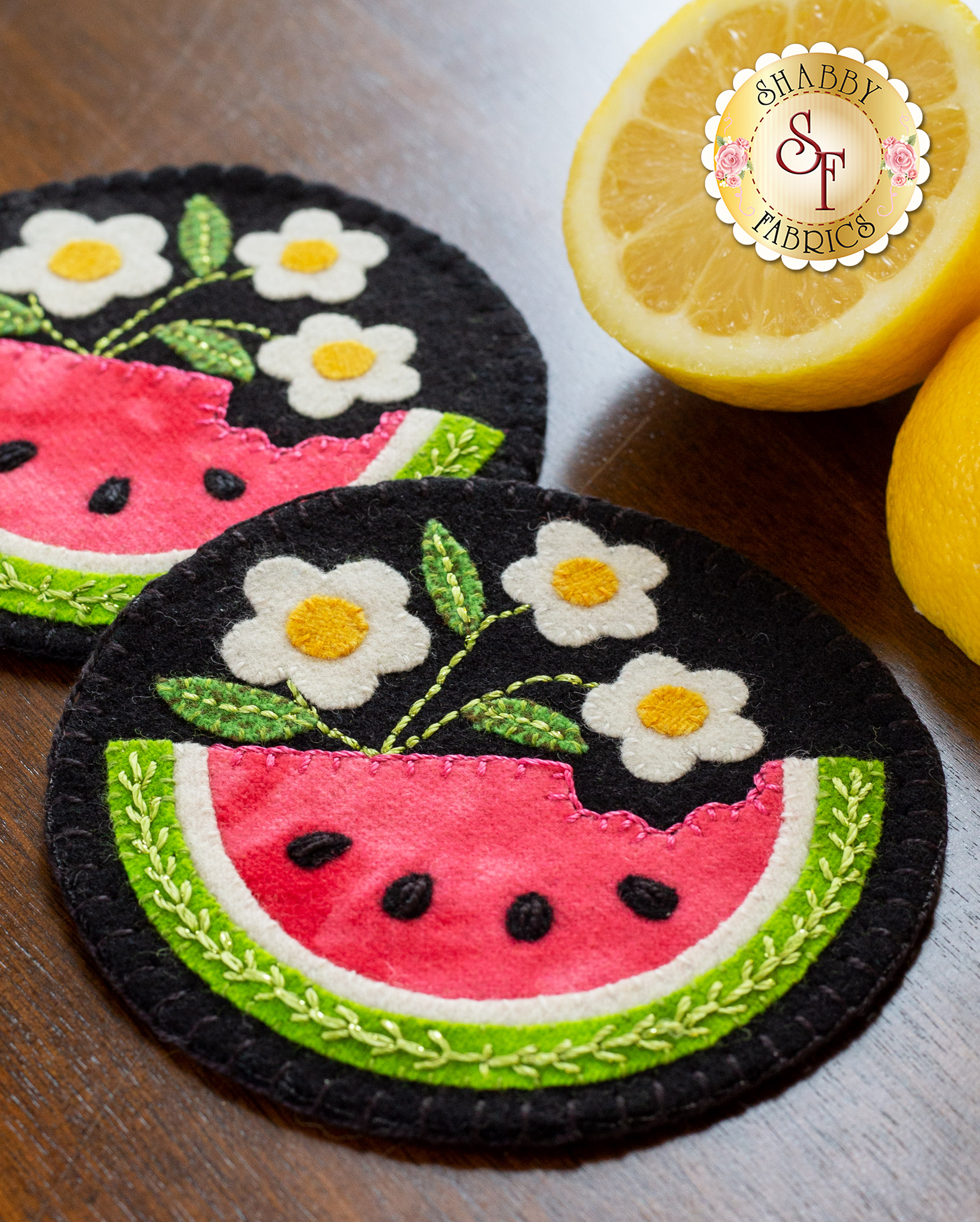 Wool coasters with watermelon appliqué on a wooden table with sliced lemons in the background.